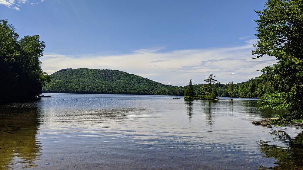 wilderness pond with small island and mountain in the background.