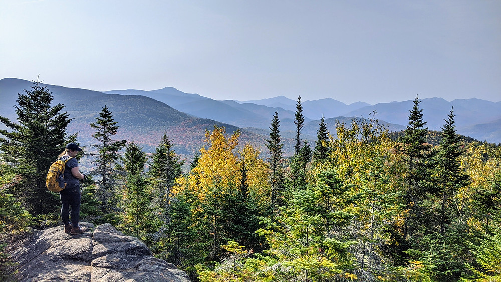 Woman looking over the mountains in fall. Vibrant colors.