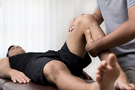 Therapist treating injured knee of athle