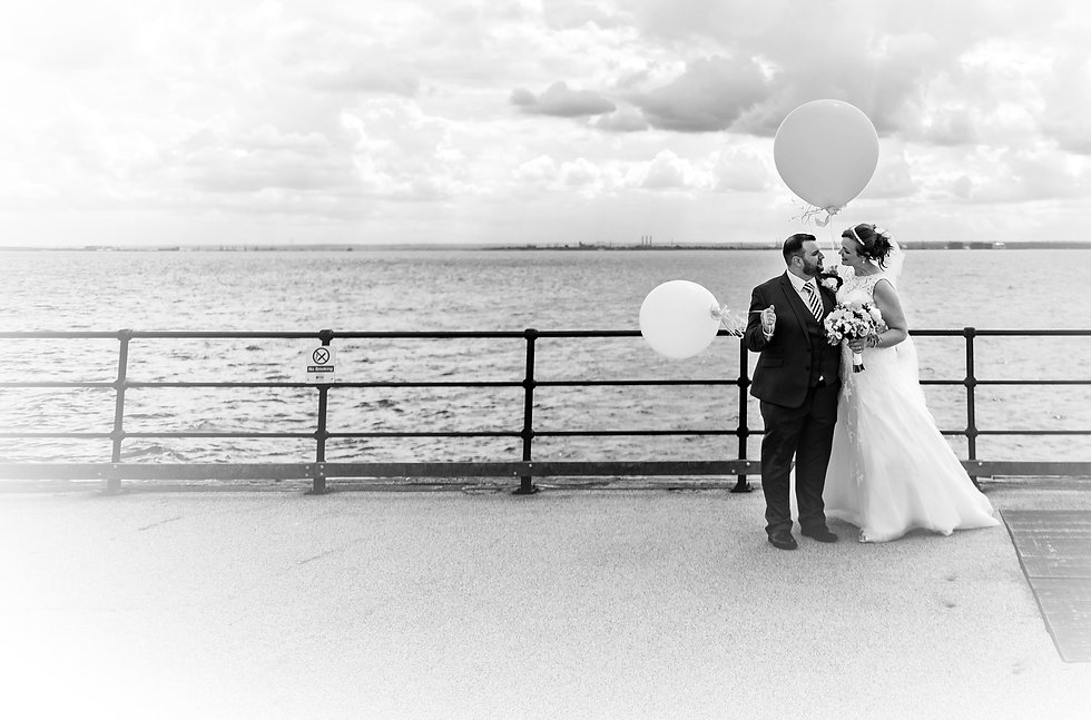Bride and groom with balloons on Southend Pier