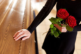 woman-with-red-roses-and-coffin-at-funer