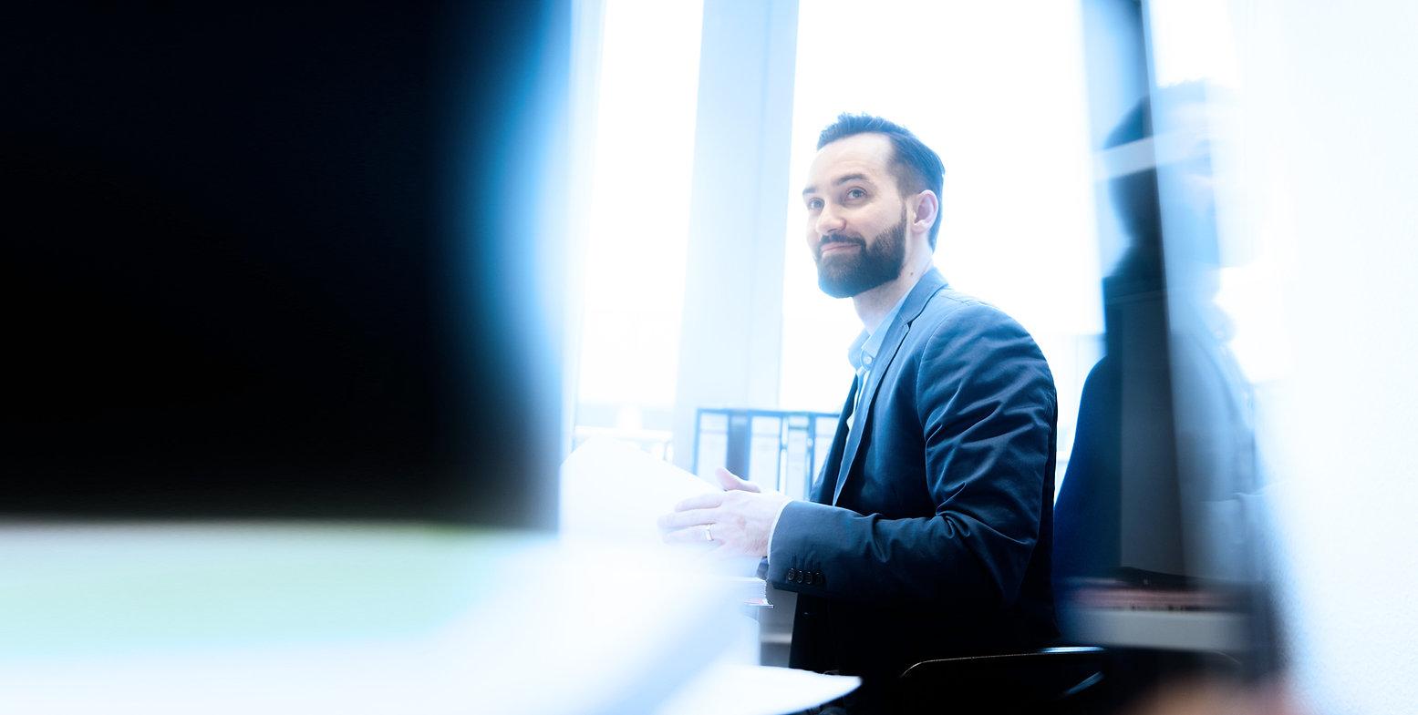 Steuerfachangestellter im Büro, entspannt, lächelnd, sympathisch