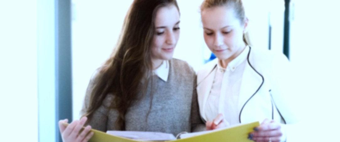 Zwei Azubis vertraut gemeinsam Aktenunterlagen ansehen, Auszubildende, zwei junge Frauen