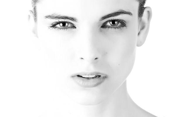 Portrait en noir et blanc d'une belle jeune femme ayant le visage dégagé.