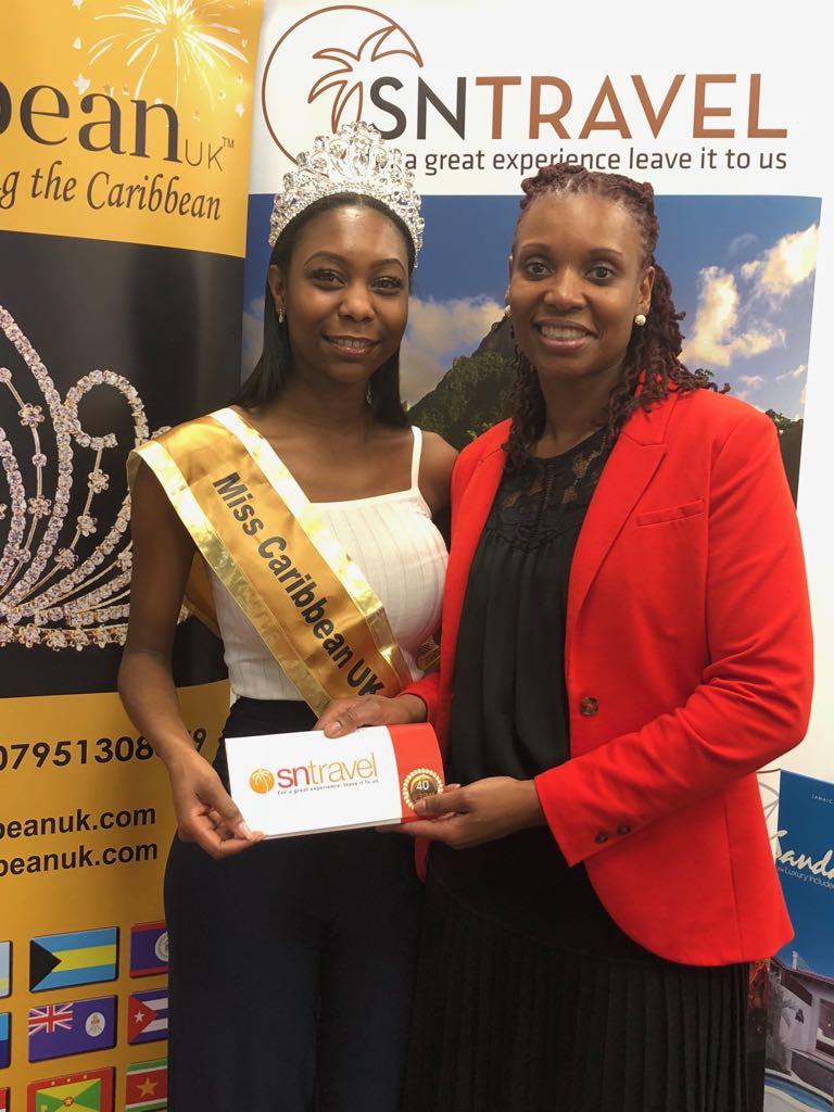 Elizabeth receives her travel tickets to Grenada from Donna Joseph, Sales & Marketing Director