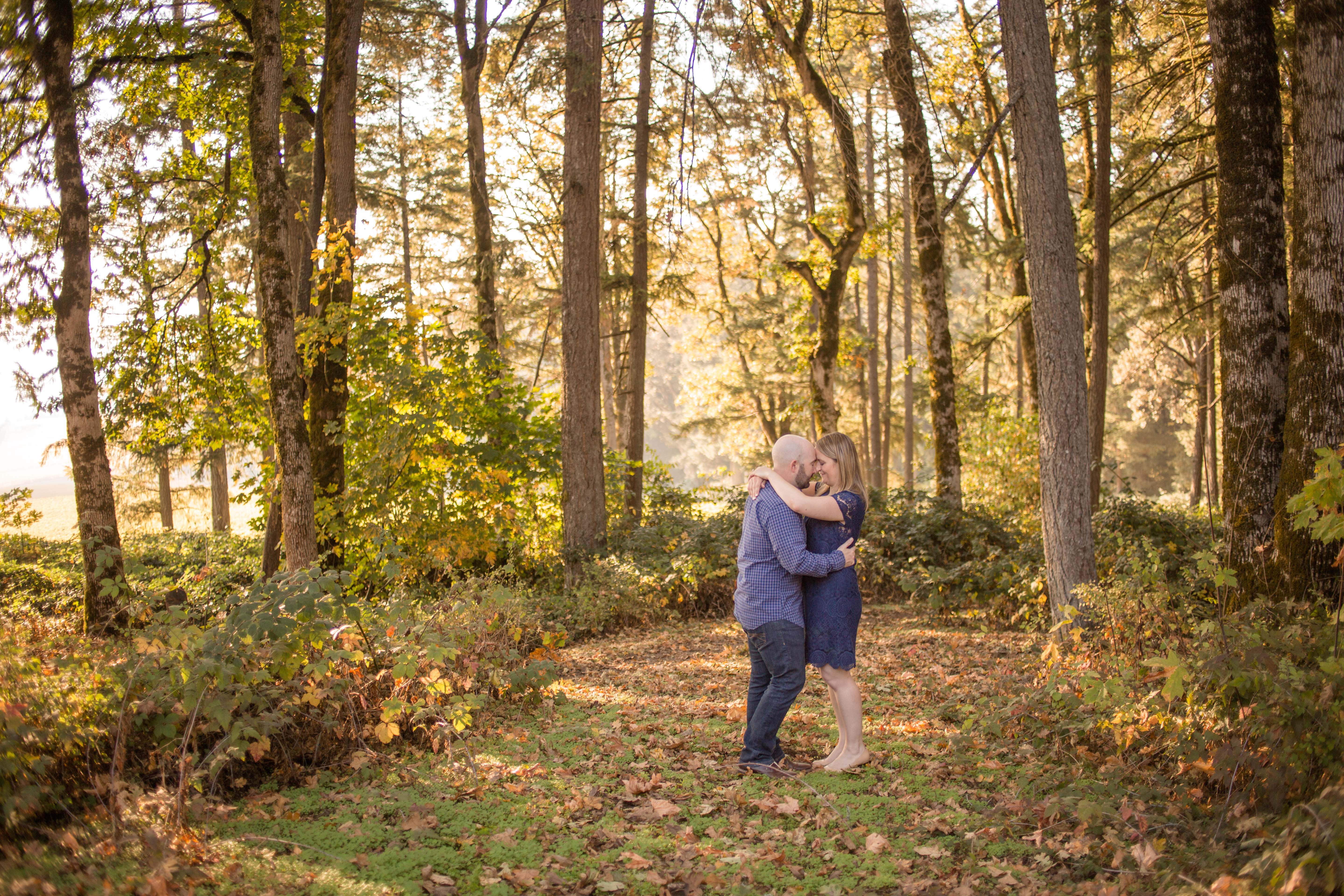 engaged couple embrace in woods
