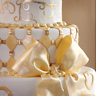 Gold ribbons and embellishments on an ivory wedding cake, photo Tracey Attlee