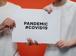 People holding pandemic COVID sign - Pho