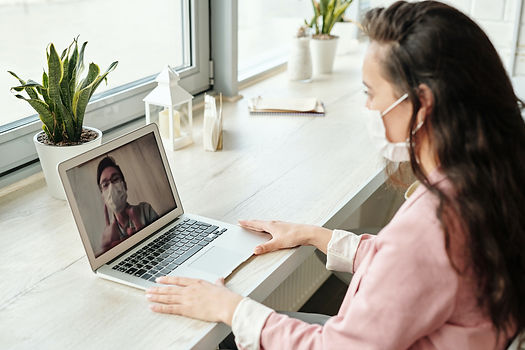 Woman in mask looking at laptop image of