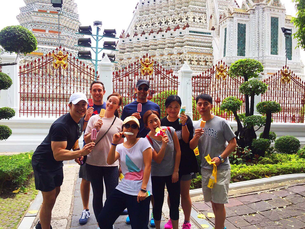 Delegates from Tybourne Capital posing for a group picture in front of Wat Arun