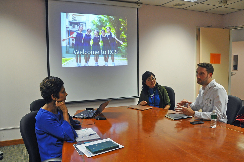 A meeting of three educations around a table. In the background is a PowerPoint slide with an image of the school.
