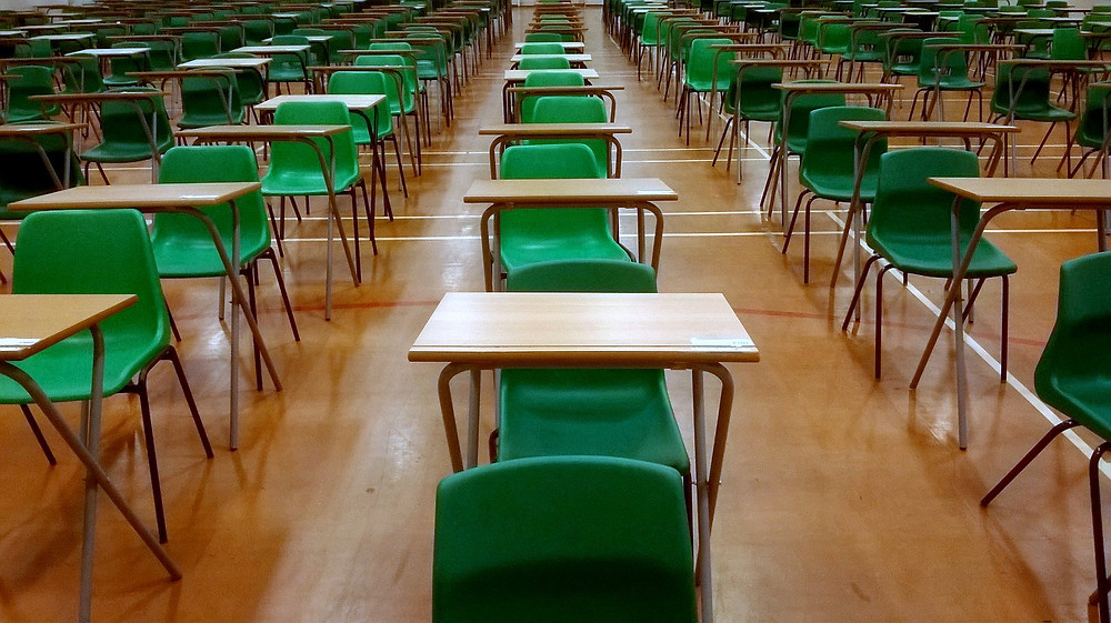 An empty exam hall with rows of desks and chairs