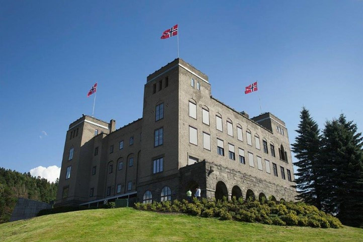 A large school building with Norwegian flags on top