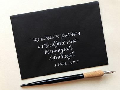 Black envelope addressed with white ink