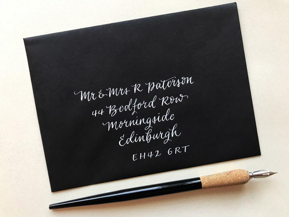 White ink on black envelope