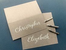 Light grey place cards inscribed with white ink