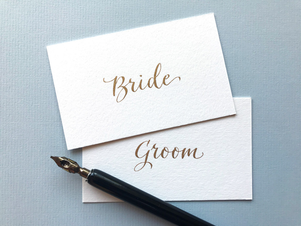 White place cards inscribed in gold ink