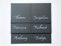 Dark grey place cards inscribed in white ink