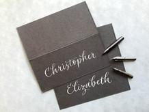 White ink on dark grey place card