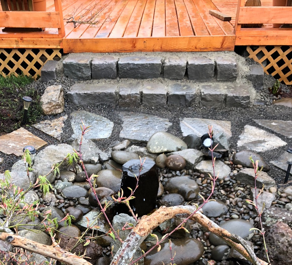 Basalt rock steps from the deck to the fountain garden.