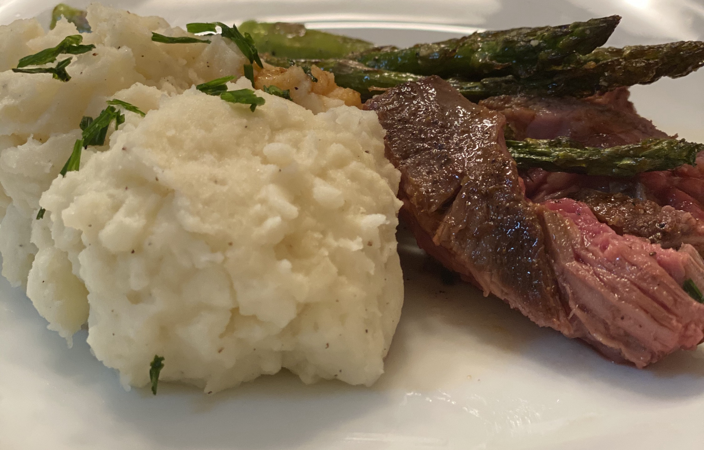 Bavette steak in a roasted garlic pan sauce, with mashed potatoes and asparagus