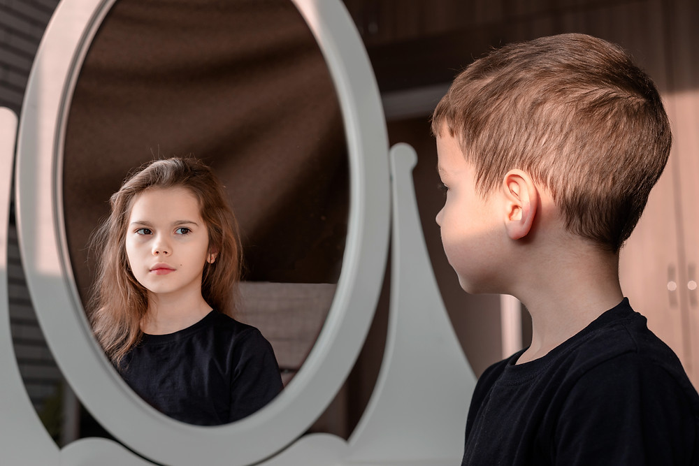 Young person looking in a mirror and seeing a different person reflected.