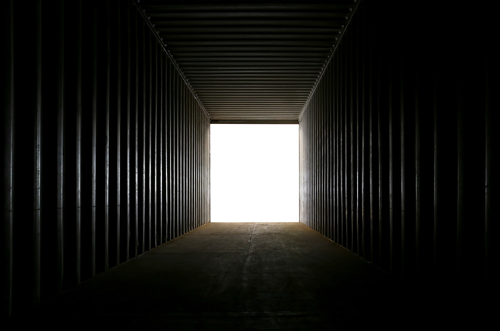 Inside a long metal container, that has very dark ribbed walls. The image focuses the lookers attention to the end of the container where there is a bright light, which contrats with the darkness inside the container.
