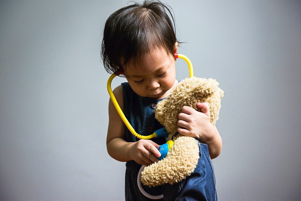 Small child, wearing a stephoscope holding a teddy bear. They are listening for the bear's heartbeat.