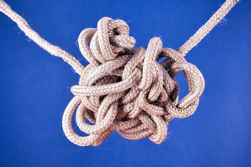 A very knotted strand of rope set against a blue background