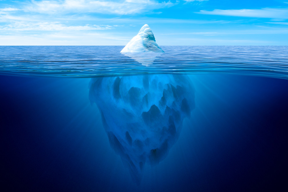 Image of iceberg, with small part of iceberg above water, set against a light blue sky. Under the water, the iceberg descends far down into the deep blue water.