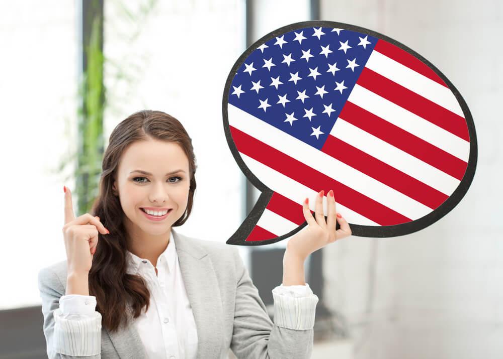Mulher que fala inglês segurando um balão de conversa com a bandeira dos Estados Unidos