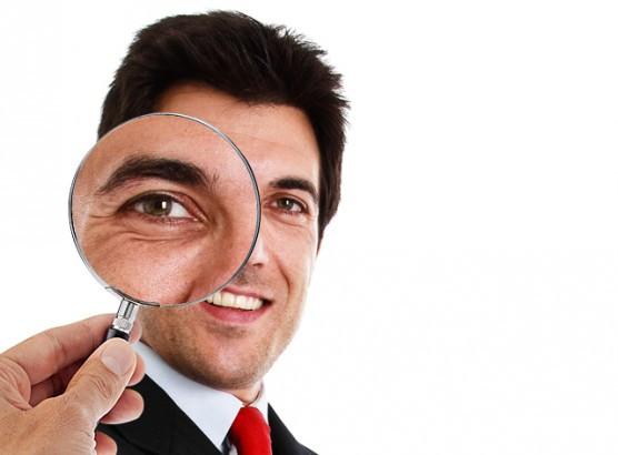 Homem executivo olhando através de uma lupa