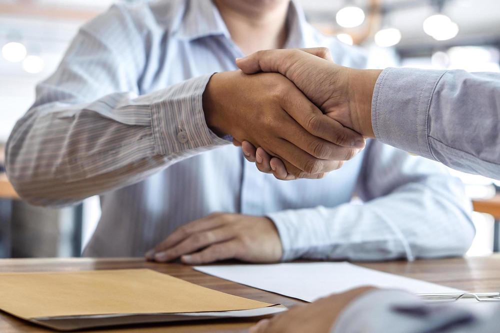 Aperto de mãos entre entrevistador e candidato, firmando um novo trabalho