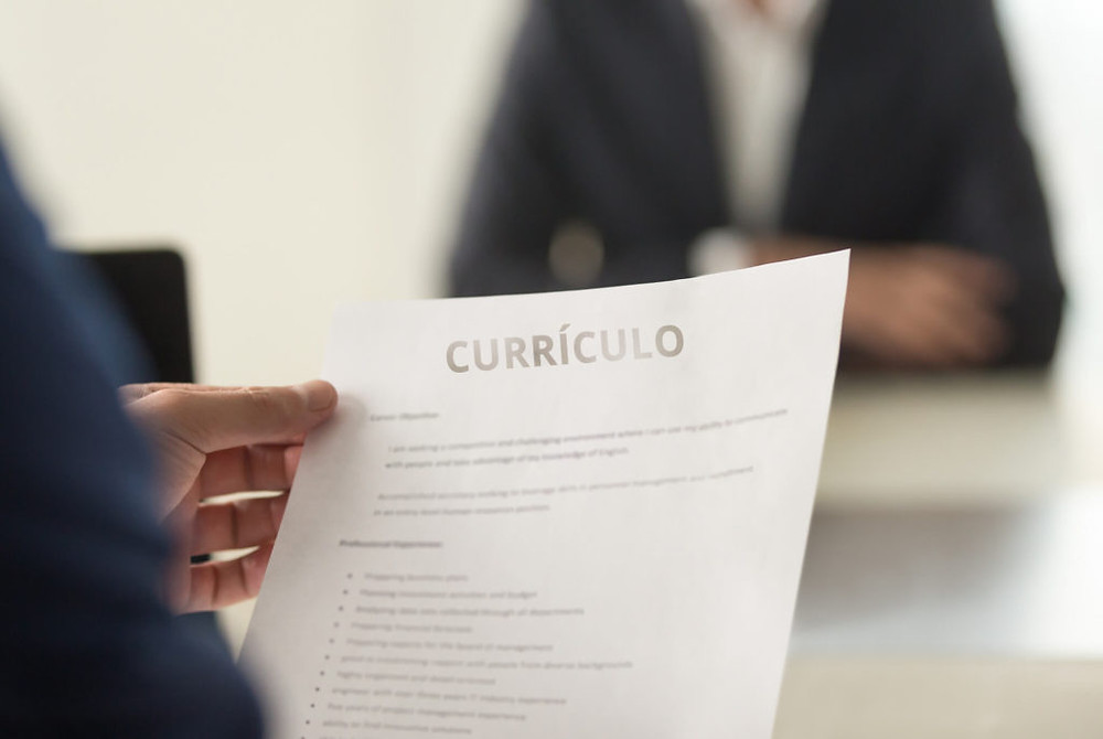 Entrevistador analisando currículo de uma candidata em meio a entrevista de emprego