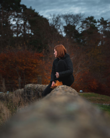 Portrait of ginger hair girl outdoors sitting on a wall Pentlands Edinburgh