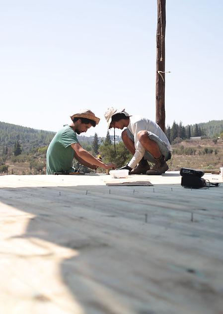 יוחאי ורפאל  בעת בניית רצפת העץ בסככה המרכזית בחווה