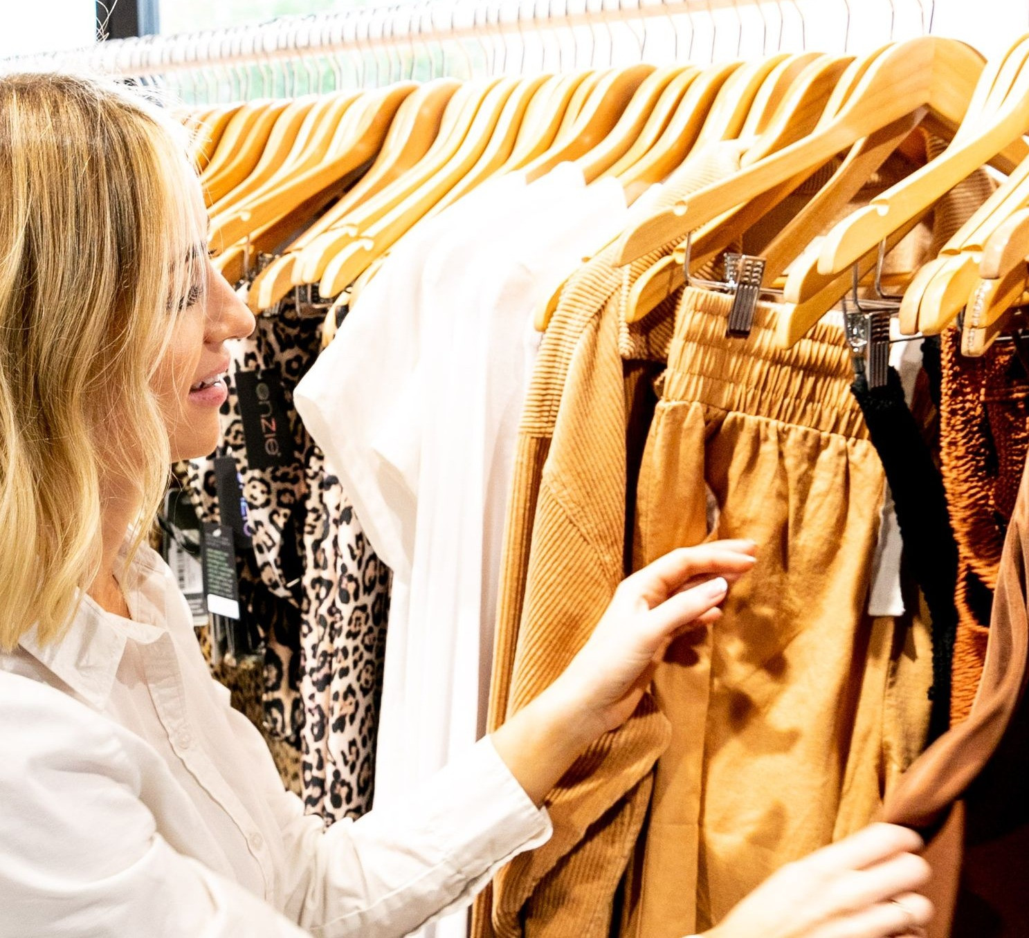 Girl looking through clothes hanging on rack
