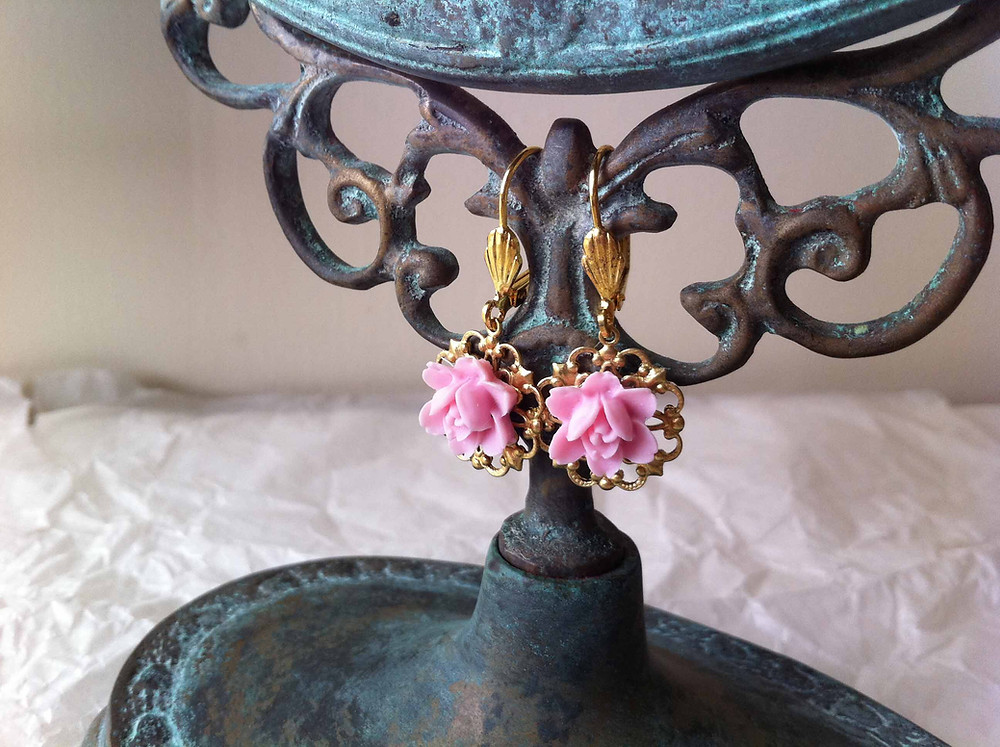 Antique Rose Earrings Hanging From Antique Decorative Frame