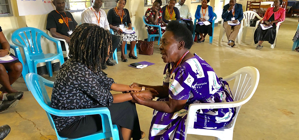 Ugandan grandmother holding a Rwandan woman's hands in the center of a circle with Uganda community leaders observing their role play of peer counseling