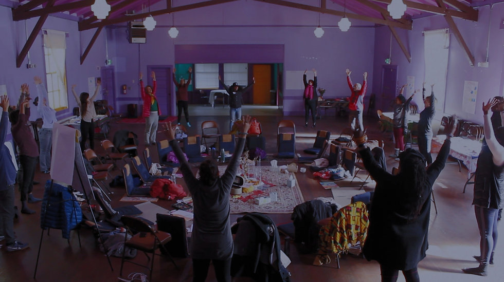 Picture of diverse people standing in a circle with arms stretched up in the air in a large purple room