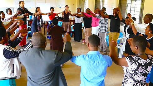 Group of Uganda community leaders as well as several Americans holding hands in the air in a circle while smiling as an elder teacher stands in the middle singing to them