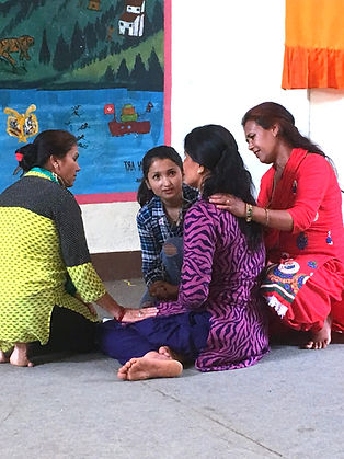 Four Nepali women practicing emotional first aid, sitting close together with arms around each other and holding hands