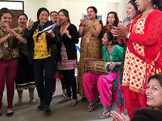 Group of Nepali women singing and clapping, with one woman playing a small drum