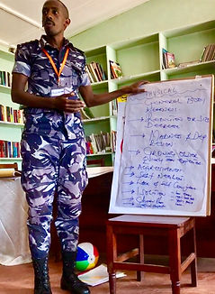 Uganda police officer wearing camouflage uniform standing in front of a flip chart which describes physical symptoms of trauma
