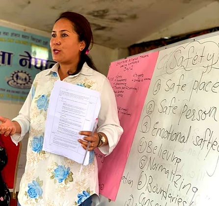 "Nepali woman facilitator standing in front of a white board teaching about Safety, with Safety written behind her on the board, along with ""safe place, safe person, emotional safety, believing, normalizing..."""
