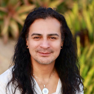 Smiling Mexican man with long hair and garden background