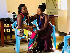 Uganda women practicing peer counseling. One woman is role playing a distressed client and the other woman is sitting near her, with arms around her.