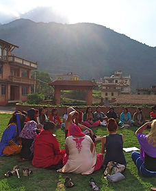 Group of Nepali women sitting in a circle on the grass at a school yard with a mountain in the background and sun shining on them