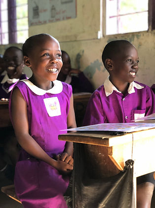 Two Ugandan school children wearing bright purple uniforms smiling with and emotions chart on their desks