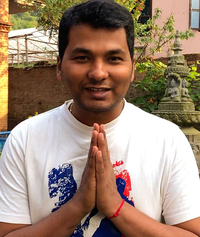"""Nepali man smiling at camera with hands in prayer """"Namaste"""" position"""